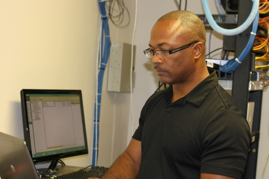 Photo by Hannah Worker  IT Specialist Anthony Brown works on getting PowerSchool up and running again.