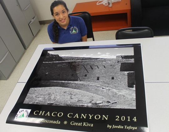 Photo by Hannah Worker --  Instagram contest winner, Jordin Tafoya poses, with the poster of her photo from Chaco Canyon.