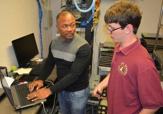 """Photo by The Catalyst IT Specialist Tony Brown and scholar Nick Mead chat in """"The Dungeon,"""" Brown's office."""