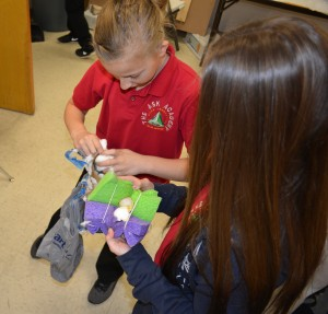 Photos by Paige Fairchild Sixth graders Isabella Chartier and Teya Schulte unwrap their egg drop packages to find a cracked egg in Mr. Grainger's Gateway to Engineering and Design class on Tuesday.