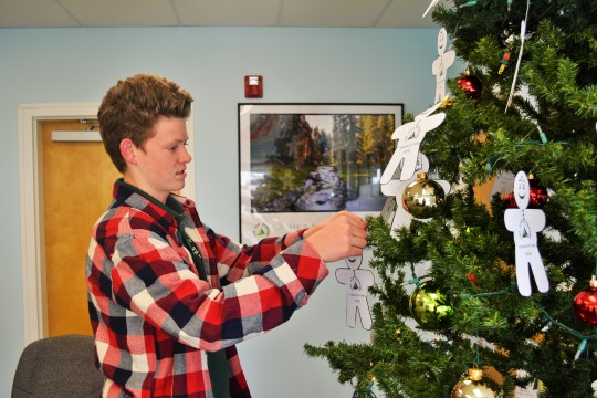 Photo By Emily Garcia Cole Jensen looks at the Giving Tree in the lobby. Deadlines to participate in the annual program is December 10.