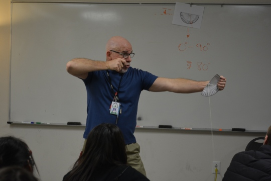 """Photo by Madison Kersey  Project Manager Mr. Project Manager Mr. Stephenson with his wild imagination of being """"Legolas"""" shooting a bow from the Shire, comparing shooting an Orc at the top of Mount Doom to the angle of elevation to reach the the top of the Sandias using an arrow."""