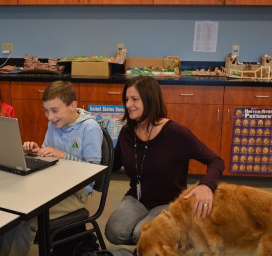 Photo by Amber Romero -- Manager Bonnie Smith, helps a scholar with her dog Bailey by her side.